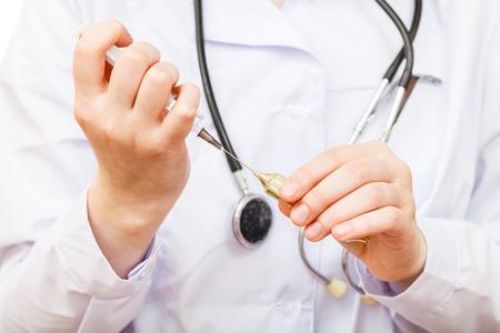 nurse fills syringe from ampoule close up photo