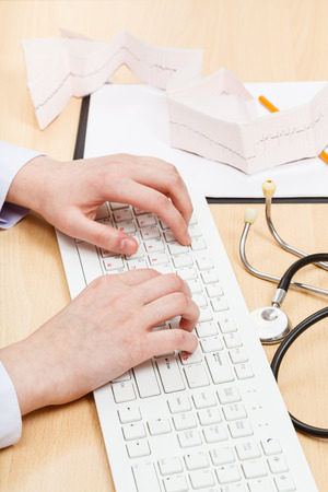 medic works on white PC keyboard close up Stock Photo