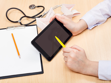 outpatient: doctor works with tablet pc during appointment Stock Photo