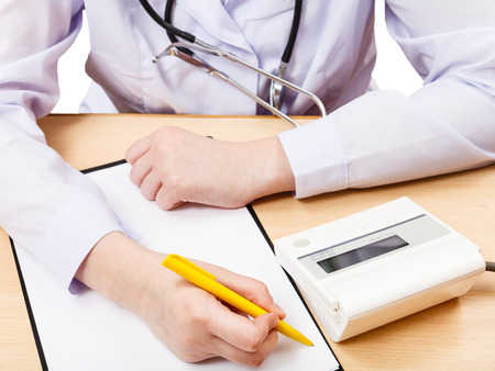 doctor measures blood pressure during appointment isolated on white photo