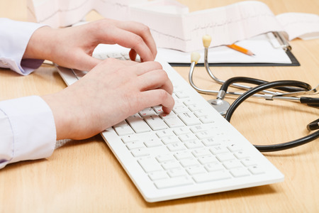 outpatient: cardiologist works on white PC keyboard close up Stock Photo