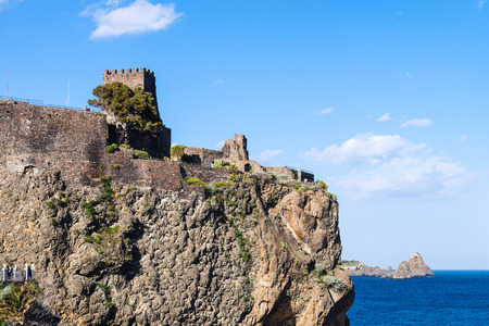 norman castle: view of Norman castle in Aci Castello town and Cyclopean Rocks (Islands of the Cyclops), Sicily, Italy Stock Photo