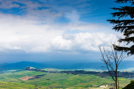 dark blue clouds over green sicilian lands in spring, Aidone, Italy photo