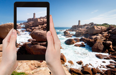 photo shooting: travel concept - tourist takes picture of lighthouse in the rocks on Pink Granite Coast in Brittany, France on tablet pc Stock Photo