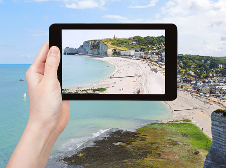 english channel: travel concept - tourist takes picture of Etretat resort village on english channel beach of cote d