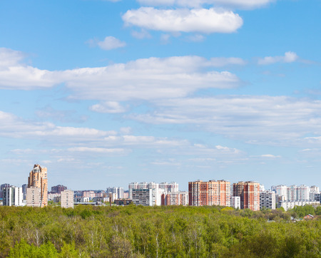garden settlement: blue sky with white clouds over city and green forest in sunny spring day Stock Photo