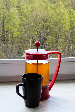 forest tea: tea kettle and mug on home windowsill and view of spring green forest outdoors Stock Photo