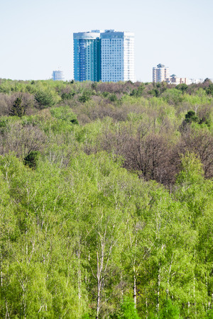 garden settlement: modern apartment house and green forest in spring day