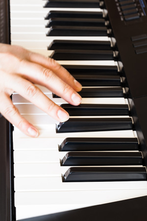 musician playing music on black and white keys of piano close up photo
