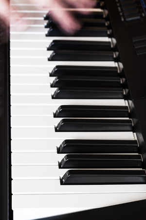 musician playing music on black and white keys of digital piano close up photo