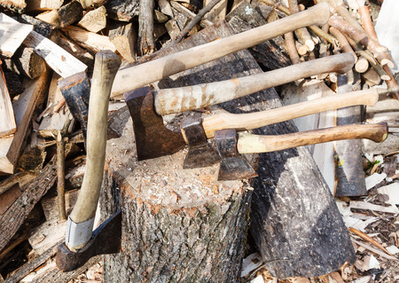farmstead: many different axes in wooden deck near pile of firewoods Stock Photo