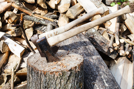 splitter: stack of wood, deck for chopping firewood, ax and cleaver on rustic courtyard
