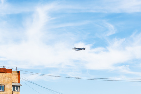 parade of homes: transport airplane in blue sky over urban house