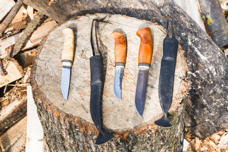 robbing: hand made hunting knives on wooden stump Stock Photo