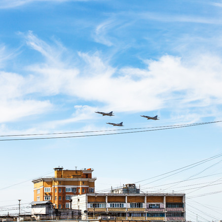 parade of homes: military aircrafts flight in blue sky over urban house Stock Photo