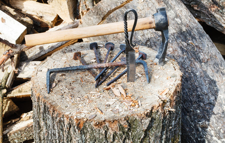 farriery: hew ax and forged hardware on wooden deck near village smithy Stock Photo