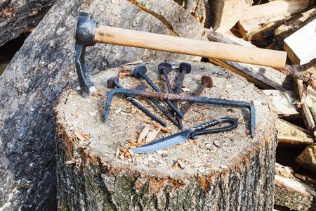ferretería: labrar hacha y herrajes de metal en el bloque de madera cerca de herrería rústica Foto de archivo