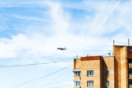 parade of homes: transport aircraft in blue sky over urban house