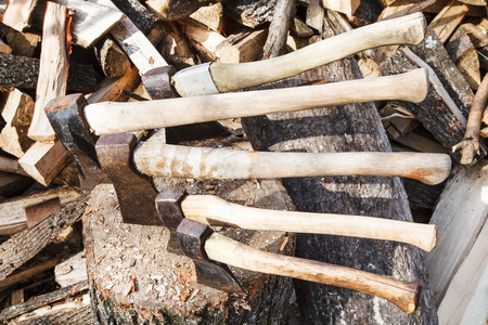 splitter: many various axes in wood block near stack of firewoods Stock Photo