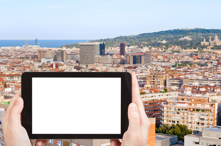 evening out: travel concept - tourist photograph Barcelona city and hill Montjuic, Spain in evening on tablet pc with cut out screen with blank place for advertising  Stock Photo