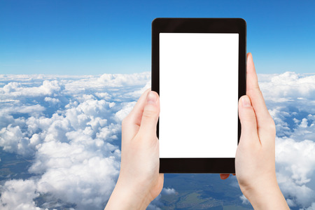 travel concept - tourist photograph above view of white clouds in blue sky and lands under clouds on tablet pc with cut out screen with blank place for advertising  photo
