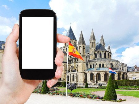 travel concept - tourist photograph medieval Abbey of Saint-Etienne (Abbaye aux Hommes) in Caen city, France on smartphone with cut out screen with blank place for advertising  Stock Photo