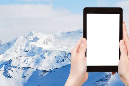 ski area: travel concept - tourist photograph snow mountains in Paradiski skiing region, Les Coches - Montchavin , France on tablet pc with cut out screen with blank place for advertising
