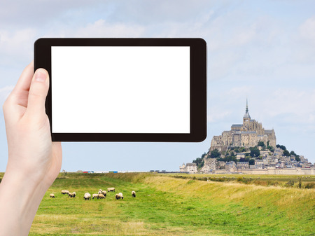 mount saint michael: travel concept - tourist photograph sheep grazing near mont saint-michel abbey, Normandy, France on tablet pc with cut out screen with blank place for advertising  Stock Photo