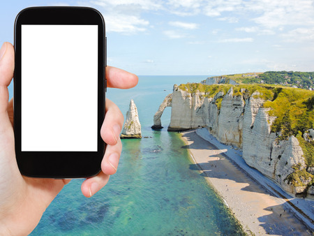 english channel: travel concept - tourist photograph english channel coast with cliffs of Etretat cote d albatre, France on smartphone with cut out screen with blank place for advertising Stock Photo