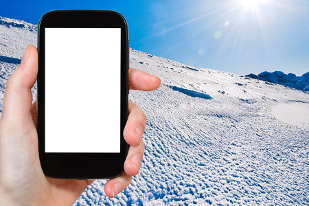 soleil: travel concept - tourist photograph blue cold snow on Alps mountain in Portes du Soleil region, Morzine - Avoriaz, France on tablet pc with cut out screen with blank place for advertising
