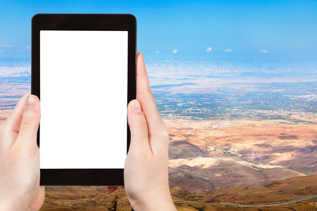 promised: travel concept - tourist photograph Palestine Land from Mount Nebo in Jordan on tablet pc with cut out screen with blank place for advertising  Stock Photo