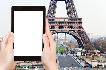 d'eiffel: travel concept - tourist photograph Champ de Mars, Pont d Iena and Eiffel Tower in Paris, France on tablet pc with cut out screen with blank place for advertising