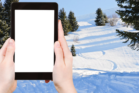 ski area: travel concept - tourist photograph skiing tracks in snow forest on mountain in Portes du Soleil region, Morzine - Avoriaz, France on tablet pc with cutout screen with blank place for advertising
