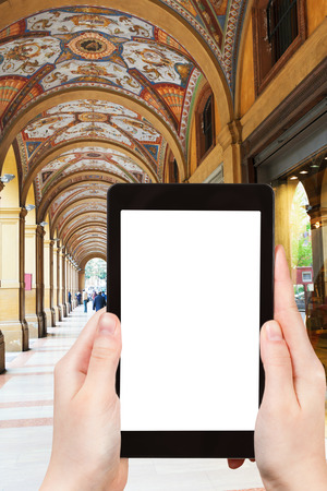 cavour: travel concept - tourist photograph medieval artistic portico on piazza Cavour in Bologna, Italy on tablet pc with cut out screen with blank place for advertising  Stock Photo