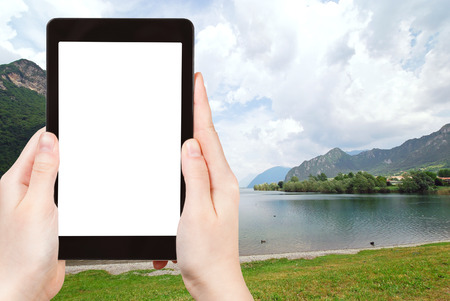 d: travel concept - tourist photograph Lake lago d idro from Idro town, Lombardy, Italy on tablet pc with cut out screen with blank place for advertising