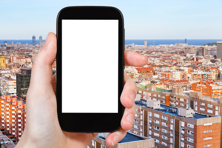 place of living: travel concept - tourist photograph above view of living district in Barcelona, Spain in evening on smartphone with cut out screen with blank place for advertising