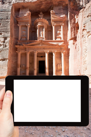 travel concept - tourist photograph temple in ancient town Petra - Treasury Monument, Jordan on tablet pc with cut out screen with blank place for advertising  photo
