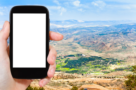 promised: travel concept - tourist photograph Promised Land from Mount Nebo in Jordan on smartphone with cut out screen with blank place for advertising