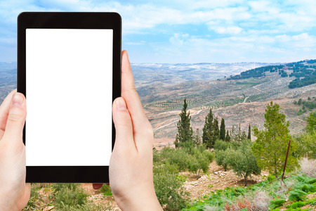 holy land: travel concept - tourist photograph Holy Land from Mount Nebo in Jordan on tablet pc with cut out screen with blank place for advertising
