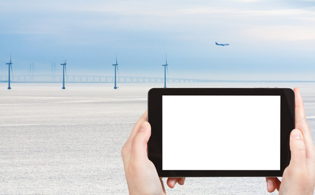 travel concept - tourist photograph Middelgrunden offshore wind farm and oresund bridge near Copenhagen, Denmark on tablet pc with cut out screen with blank place for advertising  photo