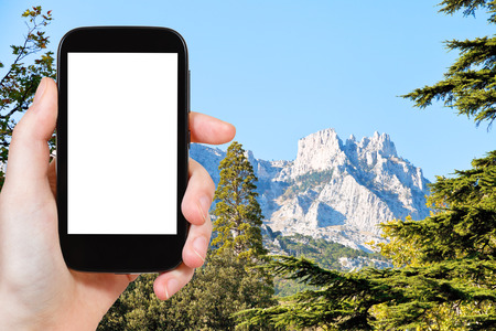 alupka: travel concept - tourist photograph Ai-Petri mountain from Alupka garden in autumn day, Crimea on smartphone with cut out screen with blank place for advertising  Stock Photo