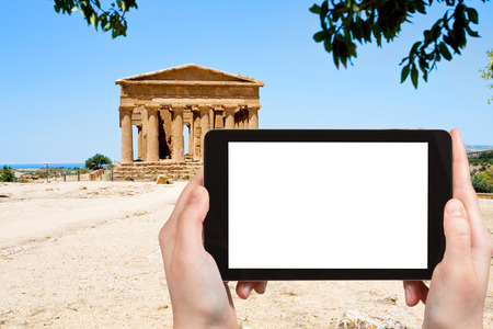valley of the temples: travel concept - tourist photograph ancient Temple of Concordia in Valley of the Temples, Agrigento, Sicily on tablet pc with cut out screen with blank place for advertising  Stock Photo