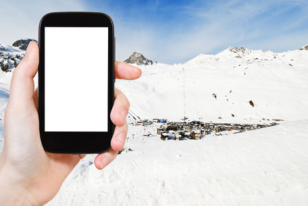 ski area: travel concept - tourist photograph view of town Tighnes between snow mountains in Paradiski region, Val d Isere - Tignes, France on tablet pc with cut out screen with blank place for advertising