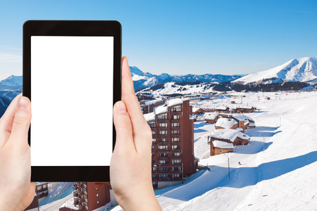 soleil: travel concept - tourist photograph above view of Avoriaz town in Alps, Portes du Soleil region, France on tablet pc with cut out screen with blank place for advertising  Stock Photo