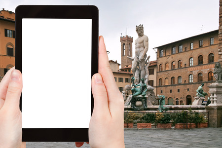 signoria square: travel concept - tourist photograph Piazza della Signoria and Fountain of Neptune in Florence on tablet pc with cut out screen with blank place for advertising  Stock Photo