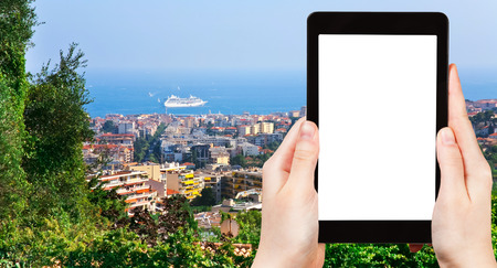 azure coast: travel concept - tourist photograph Cannes city and Azure Coast, France on tablet pc with cut out screen with blank place for advertising