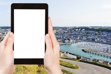 english channel: travel concept - tourist photograph Etretat town on English Channel coast in Normandy, France on tablet pc with cut out screen with blank place for advertising