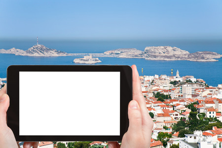 chateau d if: travel concept - tourist photograph skyline Marseille city, Franceon tablet pc with cut out screen with blank place for advertising  Stock Photo