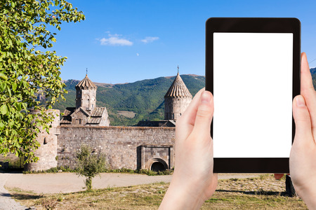tatev: travel concept - tourist photograph Tatev Monastery in Armenia on tablet pc with cut out screen with blank place for advertising