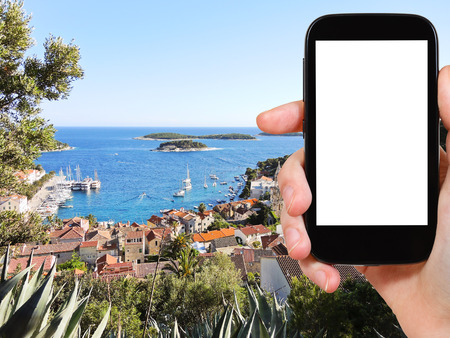 out of town: travel concept - tourist photograph town on Hvar island in Adriatic Sea, Dalmatia, Croatia on smartphone with cut out screen with blank place for advertising logo
